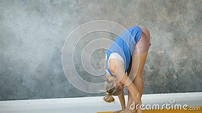 girl doing yoga surya namaskar in light studio stock