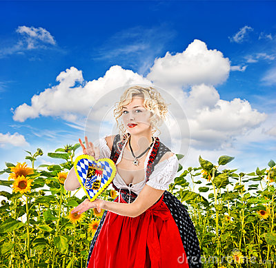 Bavarian girl in tracht dress dirndl in sunflower field