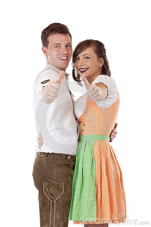 Bavarian man and woman with dirndl showing thumbs