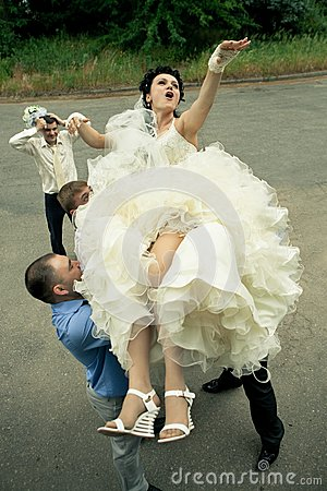 Bbride tossed by a group of groomsmen