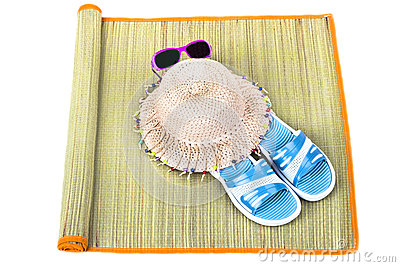 Beach accessories on straw mat over white