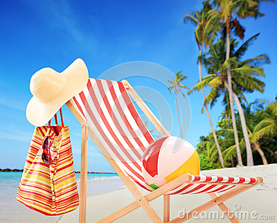 Beach chair with accessories on a tropical beach with palms