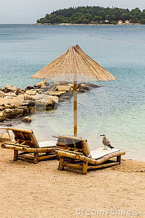 Beach chair and umbrella on sand beach. Concept for rest, relaxation, holidays, spa, resort Stock Photo