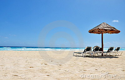 A beach chair and umbrella on a tropical beach.