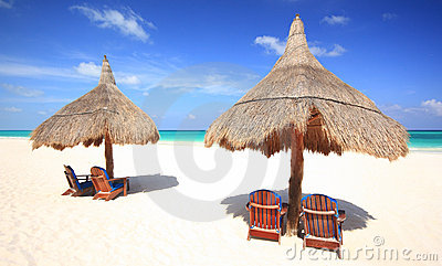 Beach chairs and thatched palapa umbrellas at reso