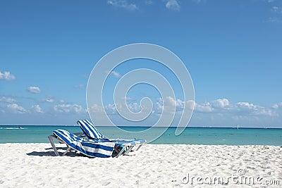 Beach chairs on perfect tropical white beach