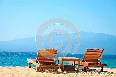 Beach chairs on tropical yellow sand beach