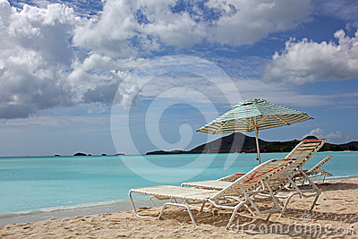Beach chairs and umbrella with copy space