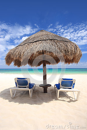 Beach chairs under palapa thatched hut