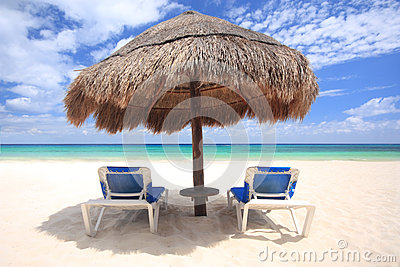 Beach chairs under palapa thatched umbrella