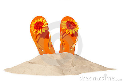 Beach concept with flip-flops on a pile of sand