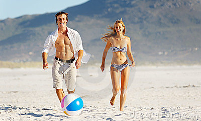Beach couple playing with ball