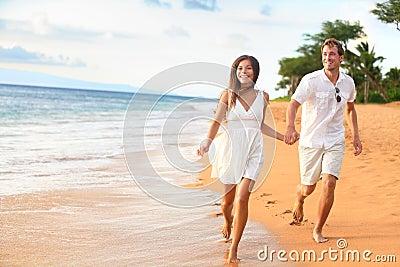 Beach couple on romantic travel honeymoon fun