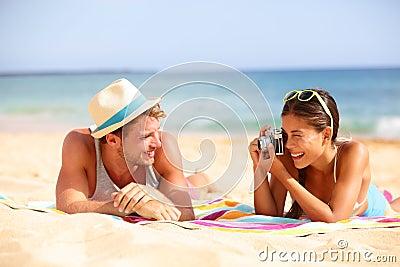 Beach fun couple travel - woman taking photo