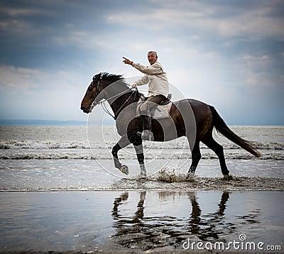 Beach horse rider pointing