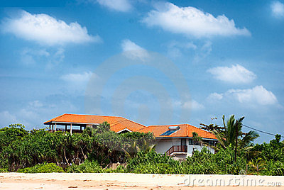 Beach house with solar panels and tropical forest