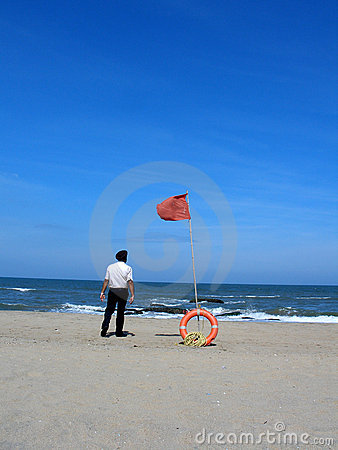 Beach with lifebuoy and man