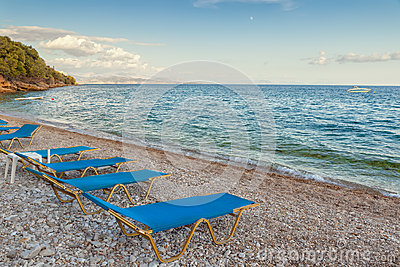 Beach Lounge chairs in the evening at the shore of Ionian sea