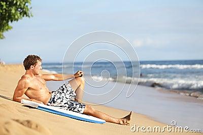 Beach man relaxing after surfing