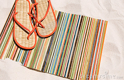 Beach mat and shoes on sand