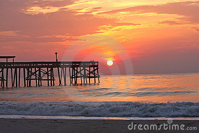 Beach with pier at sunrise