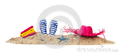 Beach sand with towels flip flops and hat