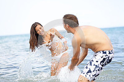 Beach summer fun couple playful splashing water