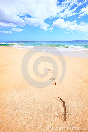 Beach travel vacation concept - footsteps in sand