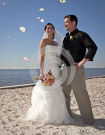 Beach wedding throwing flowers