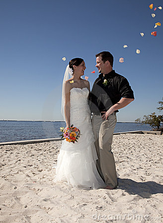 Beach wedding throwing flowers