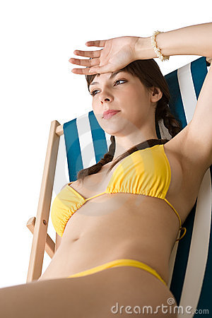 Beach - woman sunbathing in bikini on deckchair