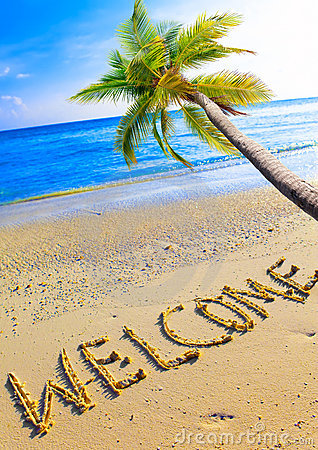 On a beach it is written Welcome and a palm tree