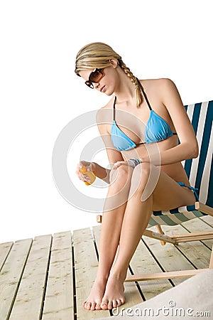 Beach - Young woman in bikini  apply suntan lotion