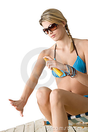 Beach - Young woman in bikini apply suntan lotion