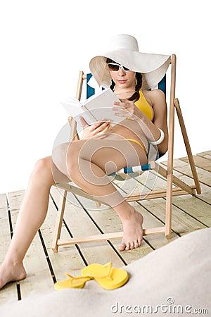 Beach - Young woman in bikini with book sunbathing