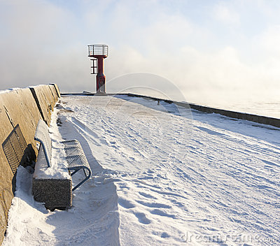 Beacon and bench on snowy mole