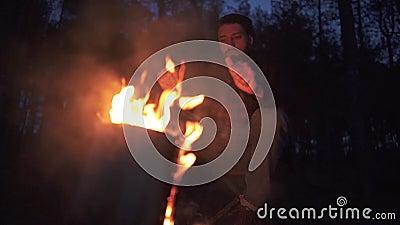 A beadred de mens zit dichtbij vuur en warmimg dient van hem omhoog het bos in duisternis in Houthakker door de brand in het bos stock footage