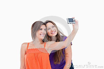 Beaming teenager photographing herself and a riend