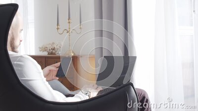 Bearded businessman working at home sitting in armchair and using computer technologies. Business, freelance and stock stock video footage