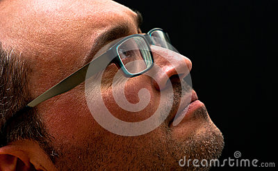 Bearded caucasian man wearing glasses looking up on black