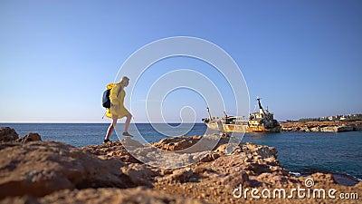Beau jeune touriste féminin dans l'imperméable jaune marchant par la plage rocheuse sur le fond de la mer pittoresque, vieux banque de vidéos