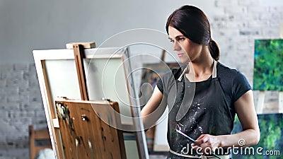 Beau peintre f?minin concentr? heureux appr?ciant dessinant l'image dans le tir moyen de studio d'art banque de vidéos