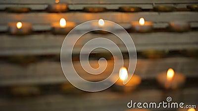 Beaucoup de flammes de bougie rougeoyant dans l'obscurité, créent une atmosphère spirituelle clips vidéos