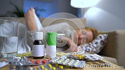 Beaucoup de pilules et médecines sur un Tableau en Front Of une jeune femme malade sur le divan banque de vidéos