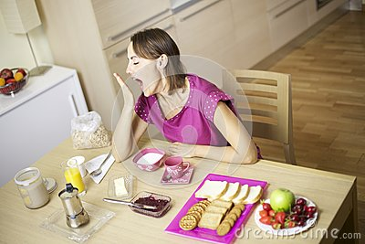 Beauitful female model yawning during breakfast