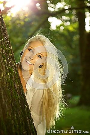 Beauté normale se cachant derrière un arbre
