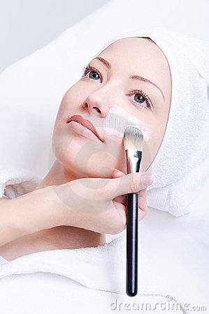 Beautician applying cosmetic mask
