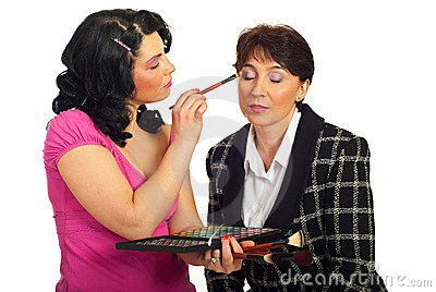 Beautician applying eyeshadow to  model