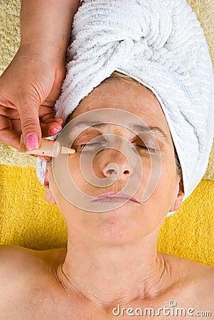 Beautician applying serum to senior face