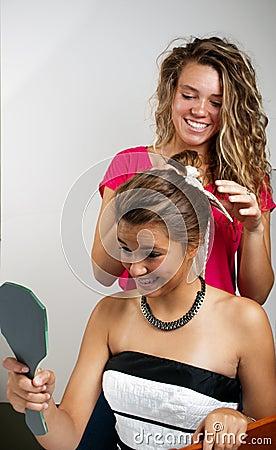 Beautician fixing girls hair